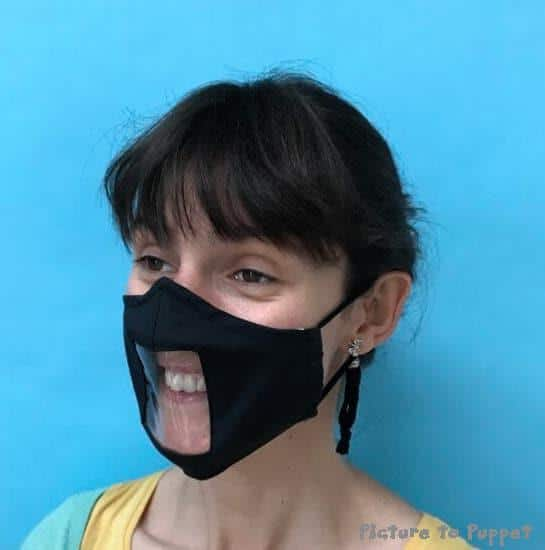 person's face wearing a black face mask with a clear window in the front