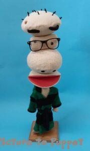 A Custom Puppet with a large nose wearing a green dressing gown on a wooden stand