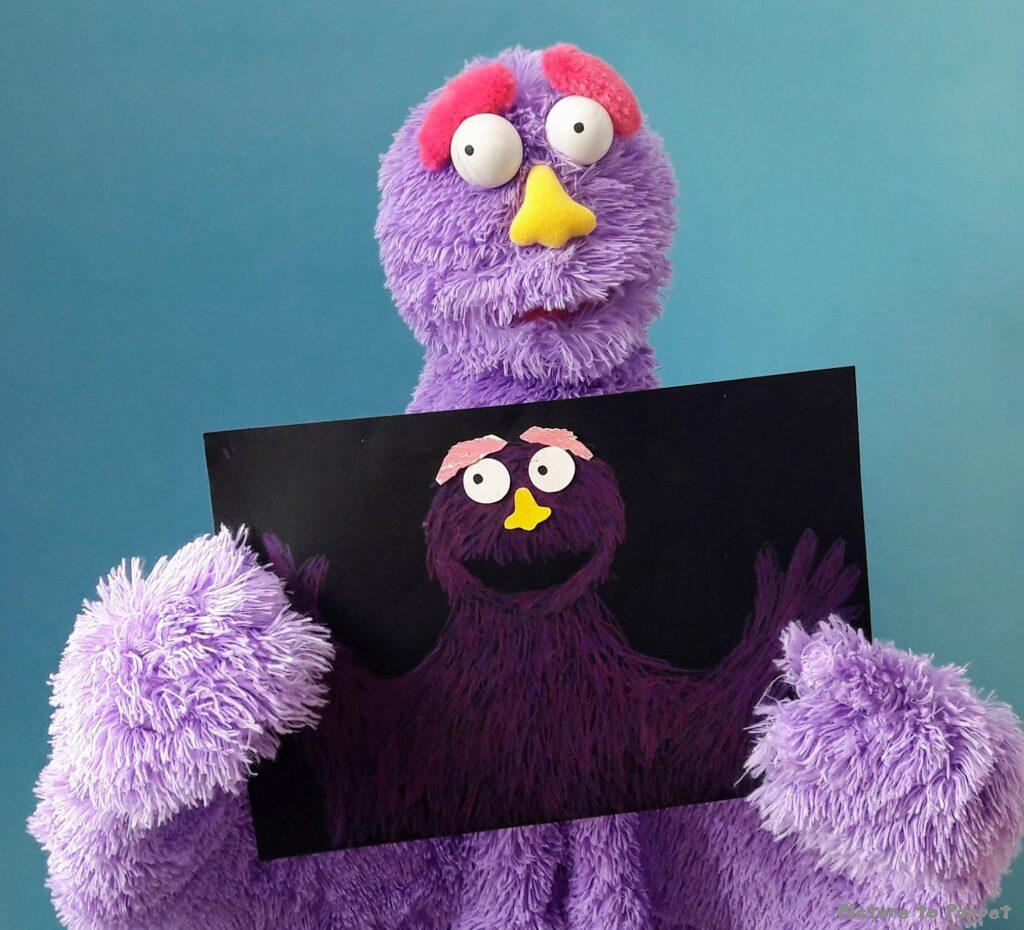 A purple puppet holding up a puppet design showing the progression from picture to puppet.